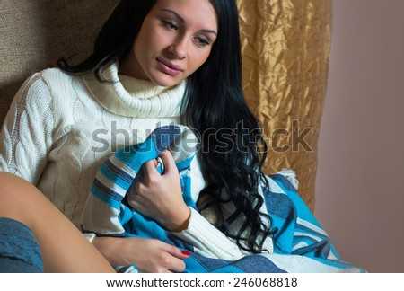 beautiful girl sitting on a couch, wrapped in a blue blanket - stock photo
