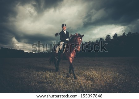 Beautiful girl sitting on a horse outdoors against moody sky - stock photo