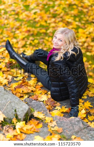 Beautiful girl sitting on a rock, autumn color leaves on the background, vertical format - stock photo