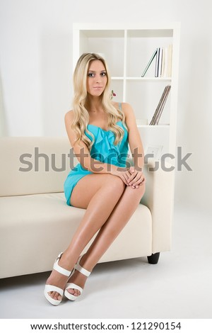 Beautiful girl sitting on a sofa - stock photo