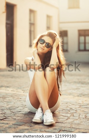 Beautiful girl sitting on a warm sunny day - stock photo