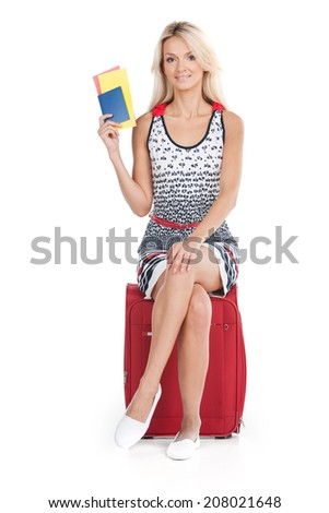 beautiful girl sitting on luggage and smiling. Young girl holding tickets on white background - stock photo