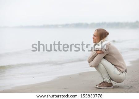 Beautiful girl sitting on the beach - stock photo