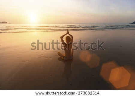 Beautiful girl sitting on the beach during sunset and meditating in yoga pose. - stock photo