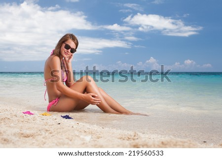 Beautiful girl sitting on the beach near the ocean
