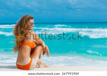 Beautiful girl sitting on the beach near the ocean. beautiful woman sitting from the back on beach.  - stock photo