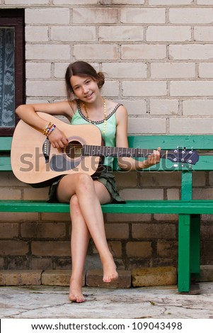 Beautiful girl sitting on the bench and playing the guitar, singing - stock photo