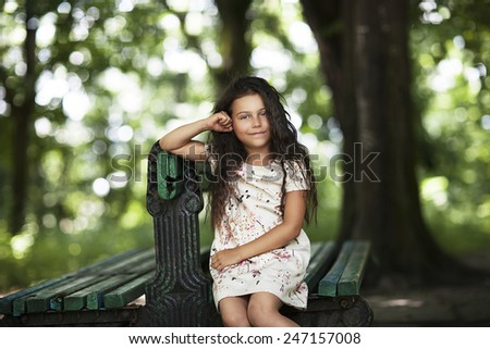 Beautiful girl sitting on the bench in the park and smiling. Happy little girl - stock photo