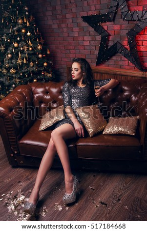 Beautiful girl sitting on the couch with cushions. After party. Christmas eve. Christmas tree. New Year. Best wishes for a pleasant and successful New Year!