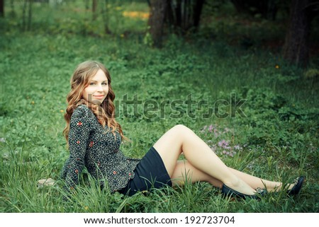 beautiful girl sitting on the grass in the flowered garden
