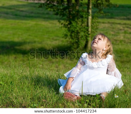 Beautiful girl sitting on the grass near tree