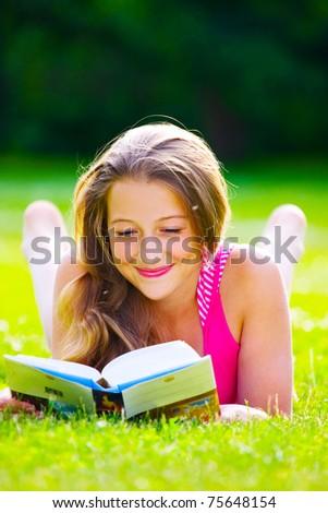 beautiful girl sitting on the green grass - stock photo