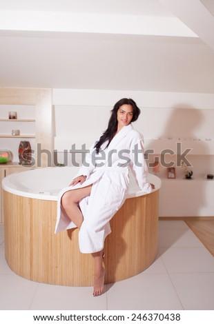 Beautiful girl sitting on the jacuzzi - stock photo
