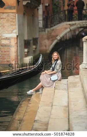 beautiful girl sitting on the stairs at the canal in Venice. Tourism, travel