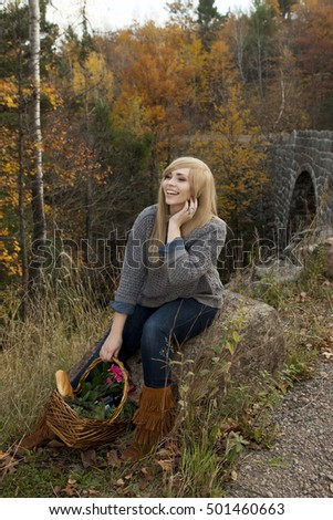 Beautiful girl sitting outdoors in autumn with a basket from the farmers market.