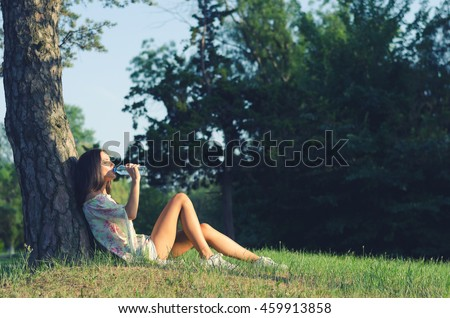 Beautiful girl sitting under the tree in nature and drinking fresh bottled water on sunny summer day.