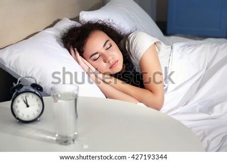 Beautiful girl sleeping in bed - stock photo