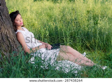 Beautiful girl sleeping in nature after reading book on sunny summer day. - stock photo