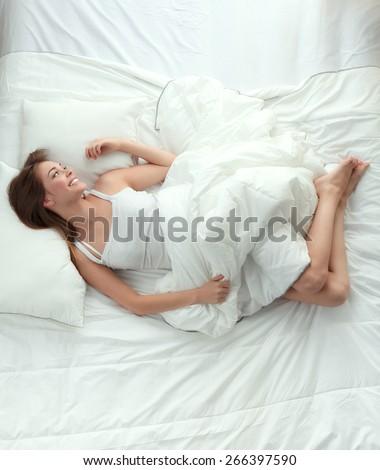 Beautiful girl sleeps in the bedroom, lying on bed . - stock photo
