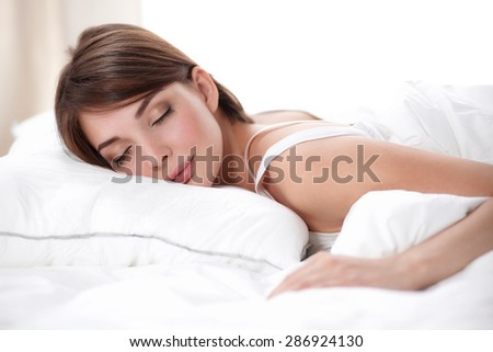 Beautiful girl sleeps in the bedroom, lying on bed.