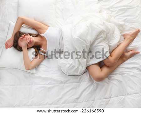 Beautiful girl sleeps in the bedroom, lying on bed, isolated