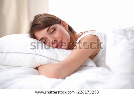 Beautiful girl sleeps in the bedroom, lying on bed, isolated - stock photo
