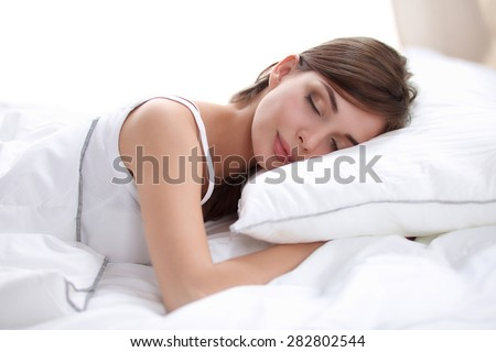 Beautiful girl sleeps in the bedroom, lying on bed, isolated - stock photo