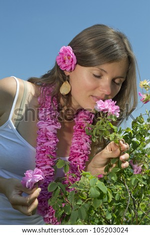 Beautiful girl smelling a rose wearing a garland of roses - stock photo
