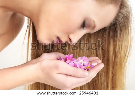 Beautiful girl smelling the flower petals in spa