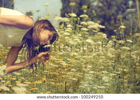 Beautiful girl smells spring flowers. Photo in old color image style. - stock photo