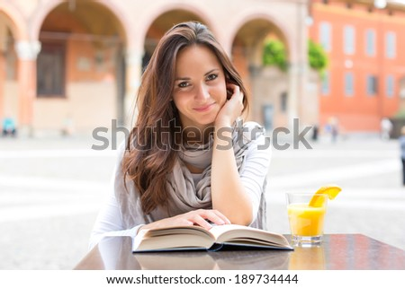 Beautiful girl smile and reading a book on a spring day - outdoor portrait - stock photo