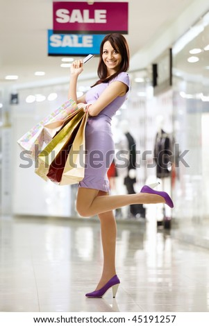 Beautiful girl smiles in shop, holding in a hand a credit card