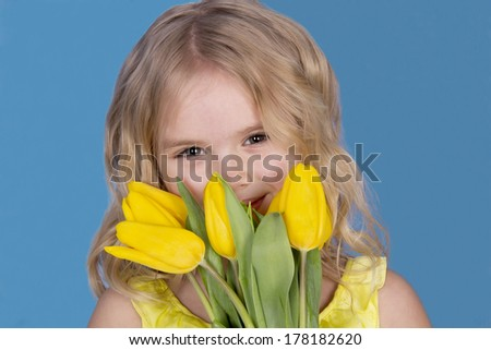 beautiful girl smiling and holding a bouquet of yellow tulips - stock photo