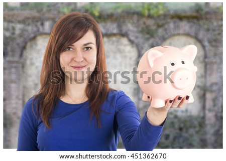 Beautiful girl smiling and holding a piggy bank on her hand