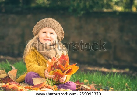Beautiful girl, smiling blonde plays with the autumn leaves - stock photo