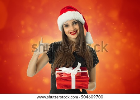 Beautiful girl smiling in santa hat with red gift in hands and showing thumbs up on red background