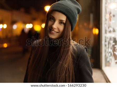 Beautiful girl smiling in the evening in the hat and coat - stock photo
