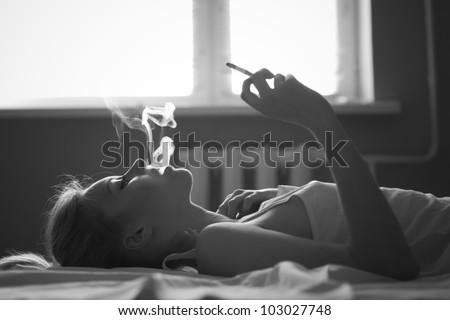beautiful girl smokes in bed - stock photo