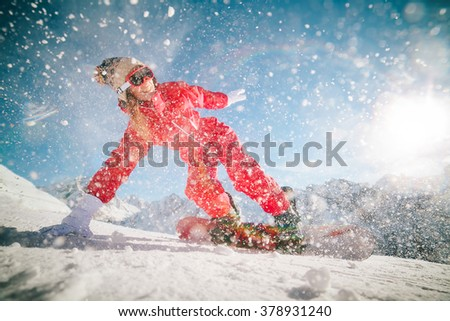 Beautiful girl snowboarding in the mountains in winter, adventure to winter sport, pretty active young woman in red clothing on snowboard - stock photo