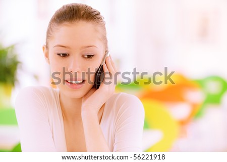 Beautiful girl speaks on mobile phone in cosy cafe. - stock photo