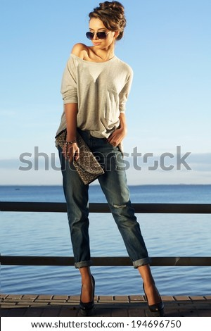beautiful girl standing against blue sea and sky and looking at you. Young stylish woman in pullover and jeans with handbag. Summer outdoor fashion portrait. - stock photo