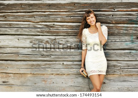 Beautiful girl standing near a wall and smiling to you - stock photo
