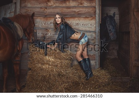 Beautiful girl standing near the stables on the straw beside her two horses. - stock photo