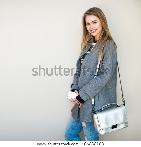 Beautiful girl standing near the wall holding a cell phone wearing casual spring outfit - stock photo