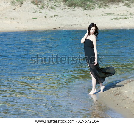 beautiful girl standing on the sandy beach in a long dress.toned