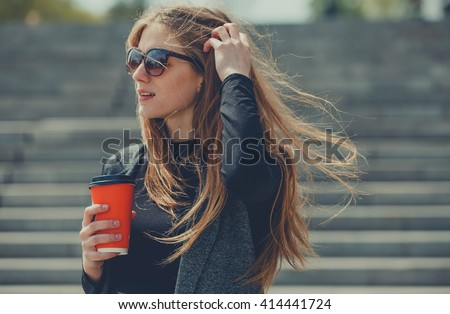 Beautiful girl standing on the street with coffee and glasses. - stock photo