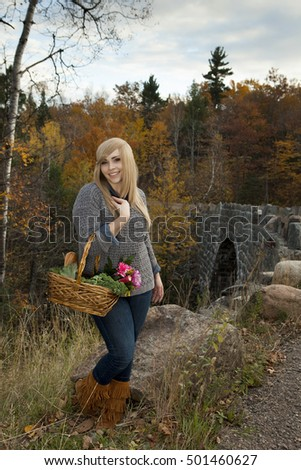 Beautiful girl standing outdoors in autumn with a basket from the farmers market.