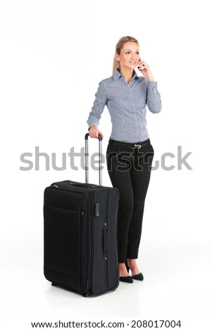 beautiful girl standing with big luggage. young girl talking on phone on white background? - stock photo
