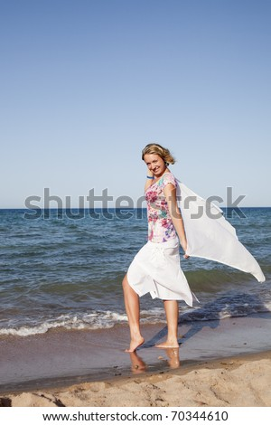 Beautiful girl standing with waving a scarf on the beach - stock photo