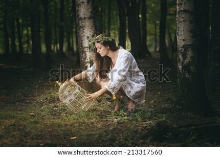 Beautiful girl staring at her fairies trap . Fantasy concept - stock photo